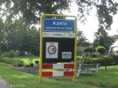 Azelo heeft officiële blauwe plaatsnaamborden (komborden) en heeft dus een eigen bebouwde kom, maar voor de postadressen ligt het grotendeels 'in' de 'woonplaats' Ambt Delden.