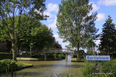 Plaatsnaambord voor de scheepvaart met aan de overkant van de Dokkumer Ee het bekende brugje.