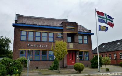 Eenrum, voormalig raadhuis uit 1930, in de stijl van de Amsterdamse School. De vlag die wappert is die van de provincie Groningen.