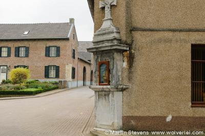 """Kijk goed om je heen als je door buurtschap Ten Esschen wandelt of fietst. Zo vind je aan de gevel van huisnr. 3 een rijksmonumentaal """"wegkapelletje in de vorm van een cenotaaf met crucifix en schelpnisje"""" uit 1767."""