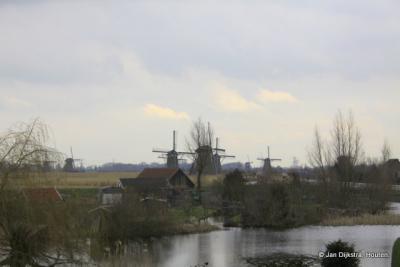 Tussen de huizen door zie je de molens van Kinderdijk al