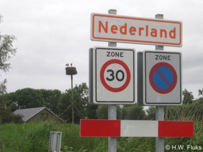 Nederland, plaatsnaambord (juli 2010) met op de achtergrond het op dat moment bewoonde ooievaarsnest. Volgens ons het enige oranje op witte plaatsnaambord van ons land.