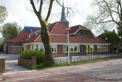 Reahûs, de verbouwde RK basisschool St. Martinus, met op de achtergrond de RK St. Martinuskerk