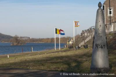 Eijsden, grenspaal en landenvlaggen aan de Maas
