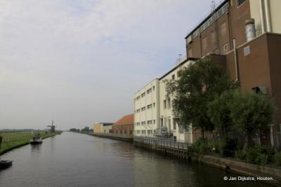 Vanaf de Scharsterbrug zien we de Scharsterrijn, met rechts de Nestléfabriek (vroeger Hollandia) en in de verte de Skarrenmoune