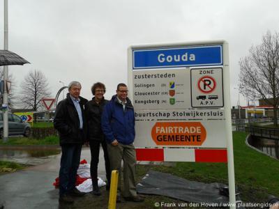 V.l.n.r.: Jaap Warners van FairTrade Gouda, wethouder Wendy Ruwhof en Co van der Horst van Stg. Buurtschap Stolwijkersluis onthullen op 21-3-2014 de nieuwe komborden van Gouda met onderbord 'buurtschap Stolwijkersluis' en het logo van FairTrade-gemeente.