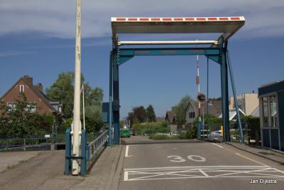 Kom over de brug en je bent in Achterbos. '30 km', staat er op het asfalt, en dat is eigenlijk nog te snel, het is daar maar smal, zoals zo vaak in waterrijke gebieden.
