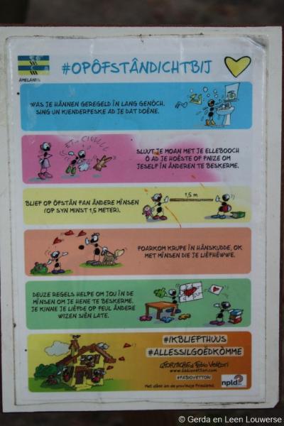 Door de uitbraak van het coronavirus in 2020 (zie https://nl.wikipedia.org/wiki/Coronacrisis_in_Nederland) is het raadzaam dat mensen een aantal dingen (niet) doen, om elkaar niet te besmetten. Op deze poster op Ameland wordt dat in het Fries toegelicht.
