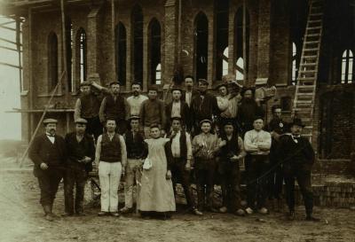 De buurtschap Barger-Oosterveld wordt een dorp door de bouw van de Gerardus Majellakerk in 1906. Hier poseren de bouwvakkers van de kerk in aanbouw even voor de fotograaf, een vrouw brengt de werklieden een bakje koffie. (© www.barger-oosterveld.nl)