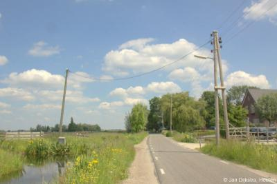 """Hier steekt een houten elektriciteitspaal in buurtschap Bilwijk de weg over. """"Aan de overkant is het gras altijd groener"""", dacht hij wellicht. Kennelijk moest aan die kant ook nog een object van stroom worden voorzien."""
