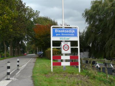 In 2013 wordt de gemeente daar kennelijk op gewezen en ziehier: blauwe plaatsnaamborden = bebouwde kom, met max. 50 km/uur. Zoals het hoort... Overigens heeft dit verschijnsel zich bij meer kernen in de gemeente voorgedaan, zoals bij Maasdijk en Westdijk.