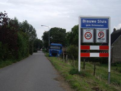 Blauwe Sluis heeft blauwe plaatsnaamborden en is/heeft dus een 'bebouwde kom', maar voor de postadressen ligt de buurtschap 'in' Lage Zwaluwe. (© H.W. Fluks)