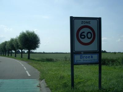 Het dorp Broek wordt door de gemeente kennelijk te dunbebouwd bevonden voor een 'bebouwde kom' en heeft daarom witte plaatsnaamborden, met 60 km-zone (© H.W. Fluks)