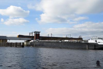 De tanker 'Vianen' uit Rotterdam is gelukkig net laag genoeg om zo onder de spoorbrug Grou door te kunnen, waardoor het schip en de trein uit Leeuwarden elkaar tegelijkertijd kunnen kruisen. (29-2-2016)