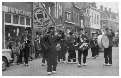 Hier nog een foto van Boerenkapel De Stroodorpers uit De Hoven in vol ornaat, met vaandel, hier in Zutphen, voor de winkel van Weekenstroo, met Jan Weekenstroo op altsax.