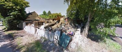 Deze boerderij aan de Dooleggersbaan in buurtschap De Hutten, in de S-bocht Booldersdijk-Dooleggersbaan-Nederweertseweg, is na een aanrijding door een vrachtwagen in verval geraakt. In 2015 of 2016 is het pand gesloopt. Hier het pand anno 2015. (© Google)