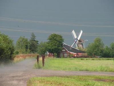 Buurtschap De Poffert, zicht op de Zuidwendinger Molen. Na regen komt zonneschijn en komt de regen als damp weer uit de grond tevoorschijn. (© Harry Perton / https://groninganus.wordpress.com/2011/07/08/een-buitje-op-de-poffert)