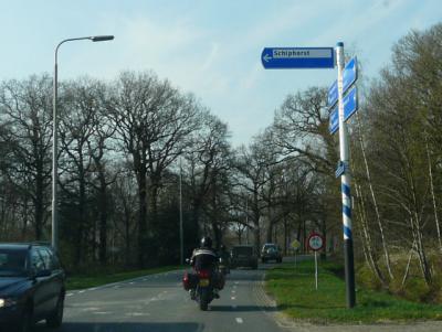 Helaas nemen wij nogal eens slordigheden waar op plaatsnaamborden en richtingborden. Dit bord is twee keer fout: De Schiphorst is mét voorvoegsel, en het is een woonplaats, en die hoort wit op blauw en niet zwart op wit te worden aangegeven.