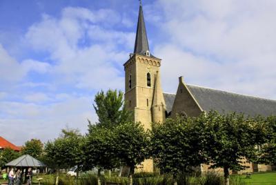 De prachtige Sint Adriaanskerk hoog en droog midden in Dreischor. Links zien we de eveneens rijksmonumentale travalje, waarin vroeger paarden werden beslagen. (© Jan Dijkstra, Houten)