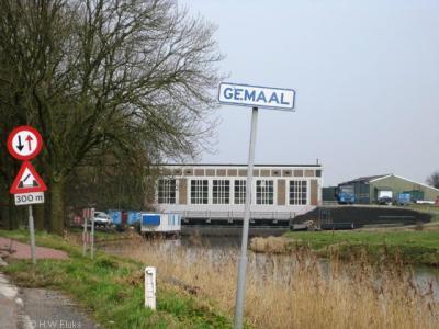 Plaatsnaambord van de buurtschap Gemaal, met op de achtergrond het gemaal waar de buurtschap naar is genoemd. Inmiddels staat er overigens een ander plaatsnaambordje, waarvoor zie het hoofdstuk Status.