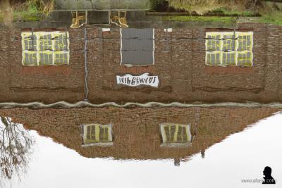 Weblogger Afanja heeft hier de weerspiegeling van een pand in het water gefotografeerd, waarbij het opschrift gespiegeld én op zijn kop staat. Het was even puzzelen, maar het blijkt dus het Tripgemaal in Gersloot-Polder te betreffen. (©https://afanja.com)