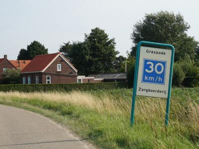 Wellicht heeft men ons verzoek van hierboven gelezen; anno 2017 staat er dit bord, vermoedelijk als aanduiding van de buurtschap én met het verzoek het gaspedaal los te laten i.v.m. de zorgboerderij alhier (formeel is hier een 60 km-zone) (© H.W. Fluks)