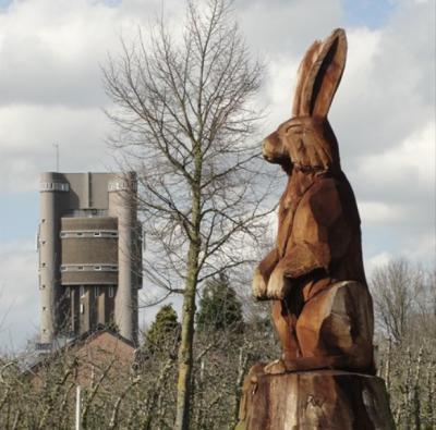 Op deze foto lijkt het net of het kunstwerk Grote Haas in de buurtschap Groot Haasdal en de imposante watertoren van het aangrenzende dorp Schimmert even groot zijn. In het echt is de watertoren vele malen groter. (© van beide foto's: www.geocaching.com)