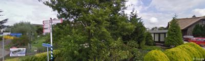 Bijzonder is dat de handvol panden van de Alphense buurtschap Heimansbuurt direct aan de bebouwde kom van het dorp Woubrugge zit 'geplakt'. Hier is dat goed te zien: het huis achter de bomen is kom Woubrugge, het rechterpand is Heimansbuurt.
