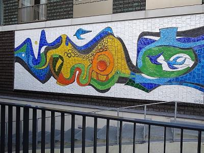 In 1970 ontwierp keramiste Maggi Giles een groot, veelkleurig mozaïek voor Verpleeghuis Coendershof in Helpman. Sinds 2015 hangt het aan de buitenzijde van het nieuwe woonzorgcentrum. (© Harry Perton/https://groninganus.wordpress.com)