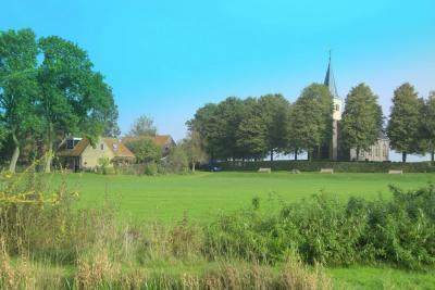 Hidaard, met de kerk nog op de terp. De rest van de terp is afgegraven en nu een prachtig kaatsveld, iets wat men daar dan ook graag doet. (© Jan Dijkstra, Houten)