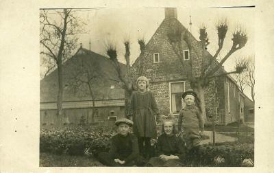 Fotokaart van boerderij te Holwinde, met de kennelijke kinderen van het gezin