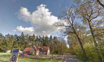 Op deze foto is goed te zien dat als je de bebouwde kom van de dorpskern van Hoenderloo gem. Apeldoorn uitrijdt, je gelijk de buurtschap Hoog Baarlo 'in' Hoenderloo gem. Ede binnenkomt (het witte plaatsnaambord op de achtergrond is Hoog Baarlo) (© Google)