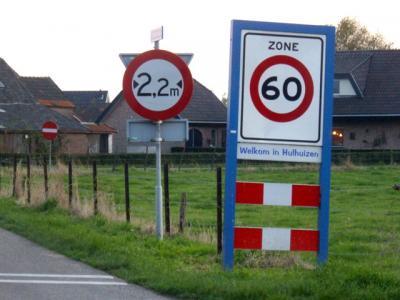 De buurtschap Hulhuizen ligt buiten de bebouwde kom en heeft daarom witte plaatsnaamborden. (© H.W. Fluks)