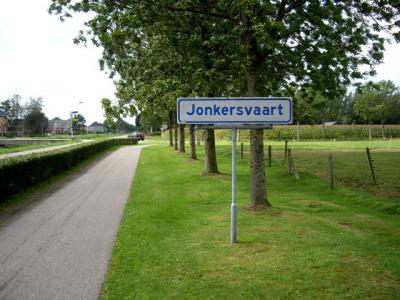 Het dorp Jonkersvaart heeft een zodanig dunbebouwde lintbebouwing dat de gemeente het geen 'bebouwde kom' vindt. Het dorp ligt dus geheel 'buiten de bebouwde kom', en heeft daarom witte plaatsnaamborden en geen blauwe. (© H.W. Fluks)