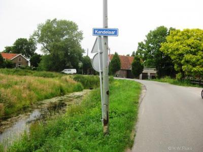 De buurtschap Kandelaar is van een wel erg 'zuinig' plaatsnaambordje voorzien. Het heeft namelijk de uitvoering van een straatnaambordje, maar dat is het toch niet, want de weg ter plekke heet namelijk Kandelaarweg.