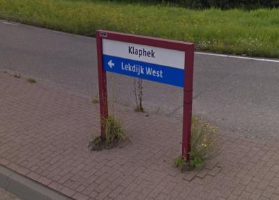 Dit is het 'format' voor wijk- en buurtbordjes in de gemeente Nieuwegein. Dit lijkt dus een plaatsnaambordje voor de buurtschap Klaphek, maar die bebouwing valt geheel onder buurgemeente IJsselstein, dus is dit kennelijk als richtingbord bedoeld. © Google