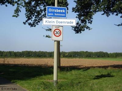Later besluit de gemeente Schinnen om buurtschap Klein-Doenrade onder de bebouwde kom van het dorp Oirsbeek te brengen, met dus blauwe borden Oirsbeek, met eronder witte borden met de naam van de buurtschap. Helaas is men daar het koppelteken vergeten...