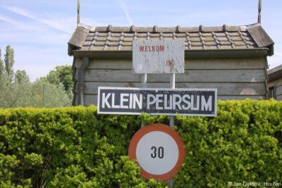 Close up van het plaatsnaambord Klein Peursum, waarmee ze je welkom heten in hun buurtschap, en, als je gemotoriseerd bent, je verzoeken je voet van het gaspedaal te halen.