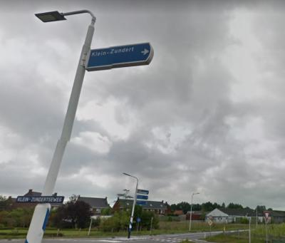Getuige dit richtingbord en straatnaambordje en de atlassen is Klein-Zundert altijd met koppelteken gespeld geweest. Toch heeft de gemeente de plaatsnaam voor BAG, postcodeboek en plaatsnaamborden vastgesteld zónder koppelteken. (© Google)