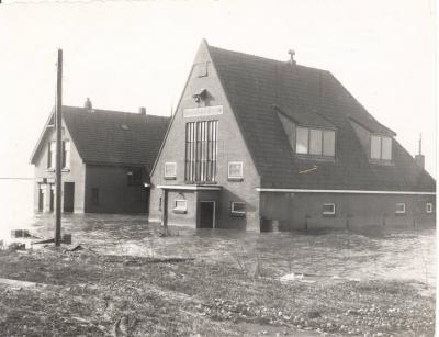 De watersnoodramp van 1953 heeft niet alleen huisgehouden in Zeeland. Ook het N hiervan gelegen eiland Goeree-Overflakke is toen getroffen. Hier zien we dat ook de kerk en pastorie van buurtschap Langstraat geen droge voeten hebben gehouden...