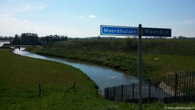 Bij het gemaal gaat de Maasdijk over in de weg Moordhuizen, wat natuurlijk ook gewoon de Maasdijk is, alleen met een andere naam. :-) Op de achtergrond een imposante zandgraafmachine van het project Over de Maas.