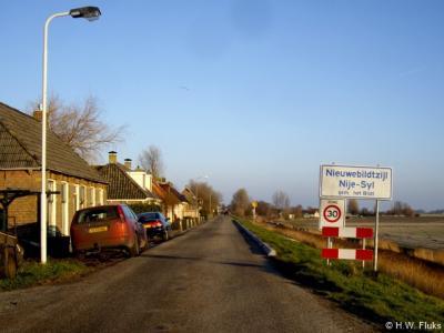 De buurtschap Nieuwebildtzijl wordt kennelijk niet dichtbebouwd genoeg bevonden voor een 'bebouwde kom' en heeft daarom witte plaatsnaamborden, maar binnen het beborde gebied wel met een 30 km-zone