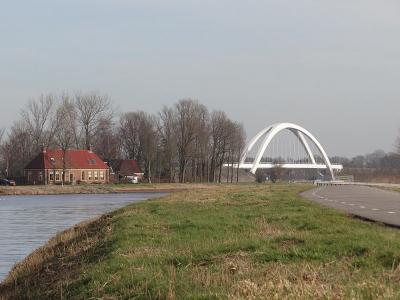 Zicht op buurtschap Noordhornertolhek, met rechts de in september 2017 geplaatste nieuwe spoorbrug over het Van Starkenborghkanaal, die in werkelijkheid iets verder weg ligt dan het op de foto lijkt. (© Harry Perton/https://groninganus.wordpress.com)