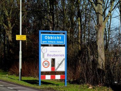 Tijdens carnaval wordt het bord met de dialectnaam van het dorp Obbicht tijdelijk vervangen door het bord met de carnavalsnaam Reuberiek. (© H.W. Fluks)