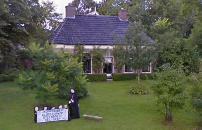 Op een Google Street View-opname uit 2010 komen wij bij toeval deze compositie tegen in de tuin van een pand aan de weg Golden Raand in Oldekerk. Als iemand weet wat hiermee bedoeld werd, houden wij ons aanbevolen. (© Google)