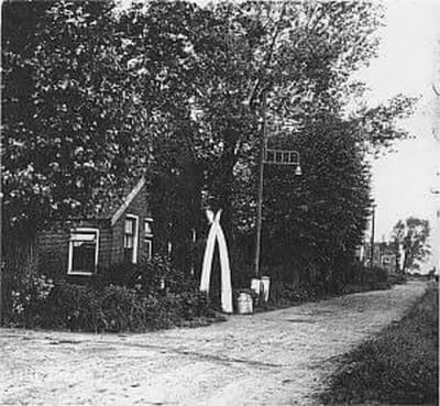 Oude Verlaat, op de voorgrond het 'nieuwe' boerderijtje op nr. 20 dat weduwe K. Prins van de verzekering heeft gekregen nadat haar vorige pand was afgebrand. Zie verder bij Geschiedenis. Het poortje voor het pand bestaat uit twee walviskaken.
