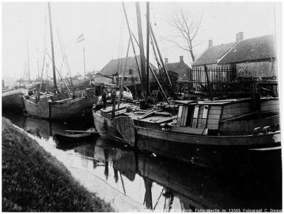 De Kerkvaartse Haven te Scharlo bij Waspik in 1900, gezien vanaf de kade naar het westen. Op de achtergrond de buurtschap Scharlo, met in het midden de timmerloods van de scheepswerf van Ruijtenberg, daarnaast het woonhuis van Adriaan Ruijtenberg.