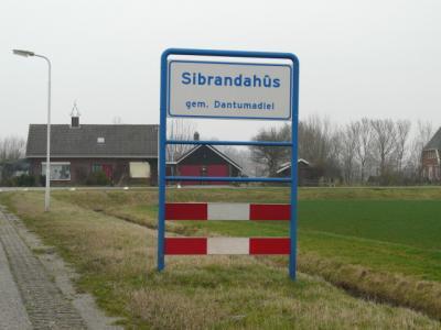 De plaatsnaam Sibrandahûs werd en wordt op allerlei manieren gespeld. Soms goed, soms verouderd, soms gewoon fout. Om het iedereen makkelijk te maken, is er sinds 2009 sowieso nog maar één spelling van deze plaats en dat is de Friese. Deze op de foto dus.