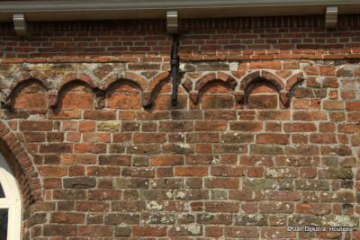Deel van de kerkmuur van de kerk van Swichum. Dat kleine steentje met afbeelding, wat zou dat betekenen?