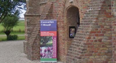 Ingang van de kerk van 't Woudt, met aankondiging van de jaarlijkse serie Zomeravondconcerten in dit 'kerkdorp'. (© Google)